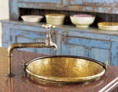 An old brass bucket set into a granite-topped island in the kitchen was converted into a vegetable sink