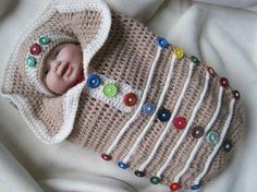 baby bundled in knit cocoon (?) with buttons