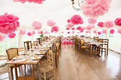 Mix soft pink tissue pompoms with bright fuchsia pink pom poms throughout a white wedding marquee.