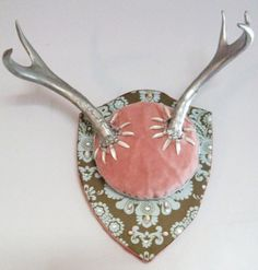 something like this, but pink antlers, white velvet (or other fabric, maybe satin), with a darker pink mount board