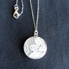 Wear your wedding dress every day with this subtle necklace design. Simply cut a small piece of lace from your gown, and enclose it in a pendant.