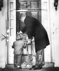 After walking around the block with daughter Caroline, who will be three 11/27/1960, President-elect John F. Kennedy helps her take her doll buggy into their Georgetown home .