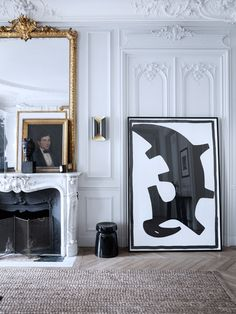 black and white interior with fireplace mantel and intricate moldings in Paris // living rooms