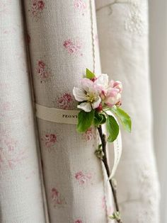 Peony and Sage -  French Florals Fabric Collection - A pink flower placed on a scroll of pink and cream floral fabric tied with a ribbon, beside off-white embroidered fabric