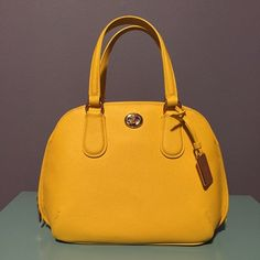 Coach Yellow Handbag NWOT!! Never used!! Beautiful bright yellow color!! This shape is to die for!! It's such a fun accessory but it also has a lot of room with one main zipper compartment, with a zipper and 2 open pockets inside, and another that opens with the turn lock featured on the front of the bag!! This will add a pop of color to any outfit!! Comes with detachable longer strap! Length: 12 inches at it longest. Depth: 4.5 inches. Height: 8 inches. Short Straps: 11.5 inches. Longer…
