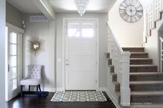 Love the clock up on the stair landing. Entryway painted in Behr Castle Path with dark oak wood floors