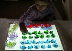 Sorting glass nuggets into empty, clear egg cartons - on the light table. I dream of having a light table! Sensory Table, Sensory Bins, Sensory Play, Play Based Learning, Learning Centers, Sensory Lights, Panel Led, Light Board, Craft Activities For Kids