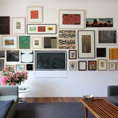 This is a great idea (if your walls can support it). The wall is actually cut out so that the TV sits flat against it with the rest of the art. There's no ugly obtrusion here, just a beautiful art wall!