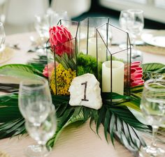 Colorful Tropical Centerpieces: Forget about having a monotone centerpiece for your jungle wedding theme. Shake things up by using ferns, wildflowers and candles to create a unique centerpiece.