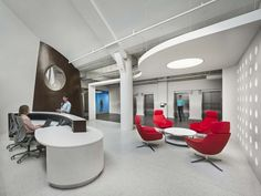 Coalesse Bob Lounge Chairs provide an inviting waiting area as well as a bright pop of red in Gogo's Chicago office.