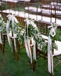 Olive-leaf garlands and satin ribbons adorned the back row of chairs.