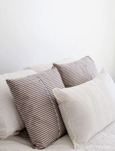 Learn how I made these farmhouse inspired ticking pillow covers over at Bellewood Cottage blog! They are so simple, easy, and inexpensive (total win). Add authentic farmhouse style to YOUR home with this quick project to make your own ticking pillow covers. #bellewoodcottage #tickingpillows #farmhousethrowpillows #farmhousedecor #cottagestyle