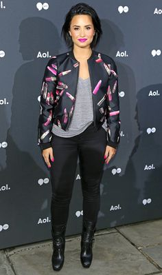 DEMI LOVATO in a lipstick print bomber jacket, gray tee and jeans at an AOL NewFont event in N.Y.C.