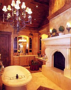 What a fantastic fireplace in a Tuscan style bathroom...and that chandelier above the tub? Yes please!
