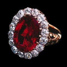 Gold ring, the hoop terminating in shoulders with scrolls and strapwork supporting the oval bezel set with a step-cut Burmese ruby ( Weight 8.48 carats) within a border of sixteen old mine-cut diamonds secured by claws. 19th century. Provenance: Queen Margherita of Italy (1851-1926), Queen Marie José of Italy (1906-2001), Gubelin Certificate 12 October 2005