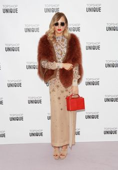Suki Waterhouse wears a floral embellished dress, fur cardigan, neutral platforms, round sunglasses, and a red top-handle bag