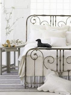 Iron scroll bed with white linens