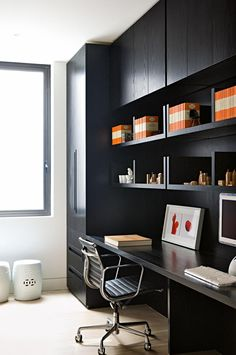 Workspace: black handleless cabinetry, shelves and built-in desk; black leather swivel chair on castors with chrome base and armrests