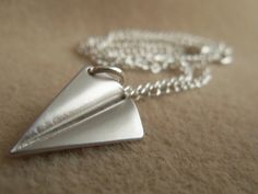 Attention all Directioners! Silver-colored paper airplane necklaces are here! This hot necklace is just like the one that Harry Styles wears. This paper airplane necklace is made out of silver-toned metals and measures in about 18 inches. If you, or anyone you know, is truly dedicated to this new band you have come to the right place! It's never too early to think about Christmas presents for you girlfriend, fellow Directioners, or best friends!