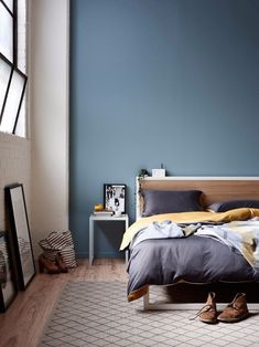 An uncompromising blue bedroom design with the classical livable detail of boots on the ground.