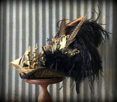Avast thar me harties! This here pirate hat be ready to set sail on thee 7 seas...er to a wedding...er tea party...er some sort er fair event. If ye be wearin this here beaut youll be turnin heads fer sure! The fabric on this hat is fabulous! Not that you can really see much of it under all those feathers! It is a lush black and gold tapestry fabric for the base. Gold compliments the hat everywhere else too! The shiny gold ship is adrift on this lovely, lovely hat! Too sophsitcated. This…