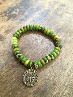 Gemstone beads create this gorgeous mix of earthy green tones featuring a lovely vintage style spanish cross coin. Beautiful contrast...