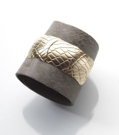 Wide leather cuff with a golden element