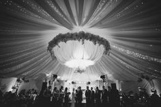Beautiful lighting and  large floral wreath in tent wedding.