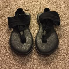 Black Sanuk yoga sling sandals The trendy Sanuk slings are super popular right now. I got these a couple of years ago but I'm not too fond of things in between my toes so while they were worn a few times, it was never for very long. Sanuk Shoes Sandals