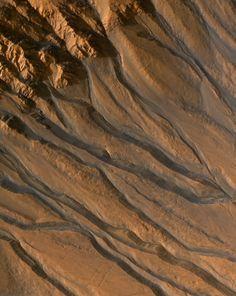 Ravines, ici en fausses couleurs, vues par la caméra High Resolution Imaging Science Experiment (HiRISE) de la sonde Mars Reconnaissance Orbiter. Le tracé sinueux des différents ravins est une morphologie typique d'écoulements d'eau liquide. La résolution de cette image est de 26 centimètres par pixel ! En savoir plus (en anglais).