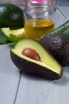green ripe avocado with leaves and organic avocado oil