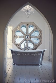 English bathroom     lovely hexagonal bathroom, with antique french bath, and an  antique window salvaged from an 18th century English church.