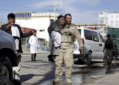 A member of the Afghan security force holds a woman while rescuing her from the site of an attack in Mazar-i-Sharif, April 9, 2015. Militants armed with rocket-propelled grenades and other weapons stormed a court in Afghanistan's northern city of Mazar-i-Sharif on Thursday, killing the district police chief and two other officers, authorities said. Anil Usyan / Reuters