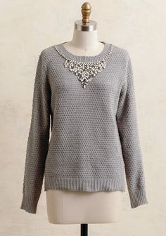 The perfect mix of classy and glam, this gray sweater is crafted in a cozy knit design with fitted long sleeves and ribbed hemlines. Adorned with white and slate-hued faux gemstones along the rou...