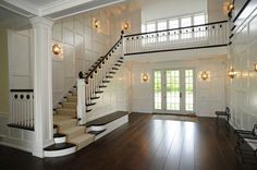 entrances/foyers - wide wood plank floors staircase sisal stair runner  Hamptons Real Estate - Grand foyer with wide wood plank floors, iron