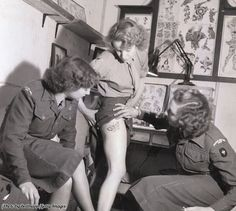 Women's Royal Army Corps member showing new tattoo on leg to fellow enlistees in WWII