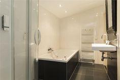 Badkamer onder schuin dak met douchecabine, groot ligbad en designradiator