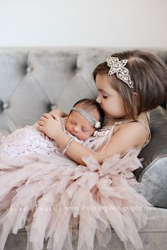 Precious photo of a big sister cuddling and her baby sister.