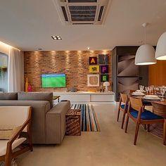 Living integrado, destaque para o tijolinho da parede do home com iluminação direcionada. Iluminação localizada na mesa de jantar.