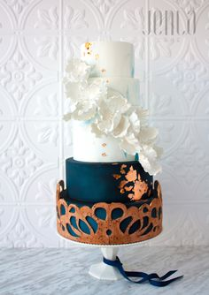 This cake features hand cut cork detailing over navy and blue marbled tiers. White sugar flowers lighten up the look while hints of copper add a modern touch. Weddingbells Canada's Prettiest Cakes 2016.