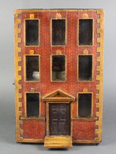 Lot 262, A 19th Century Naive dolls house in the form of a 3 storey building, the interior fitted 2 rooms complete with various furnishings, est £200-300