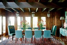 Turquoise upholstered chairs and three large pendants increase the drama in this large dining room.  via House of Turquoise: John Oetgen designer