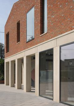 Influenced by ecclesiastical and monastic architecture, this school building in Somerset, England features a row of brick gables that sit on top of a concrete colonnade.