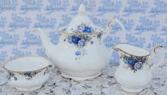 Vintage bone china tea set from Royal Albert in beautiful Moonlight Rose pattern and was manufactured in England in 1987. The tea set consists of full size teapot, milk jug and open sugar bowl. The Moonlight Rose pattern consists of gorgeous bouquets of roses in various shades of blue complemented by rich gilding both peppered gilding and delicate gilding to base, spout, handle and finial of lid. The background china colour is white The tea set pieces are in excellent, pristine condition…