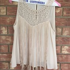 Tassel cream tank this shirt has never been worn. Looks so cute with jeans and boots or shorts. it fits smaller, it is a large but becomes a crop top Soprano Tops Tank Tops