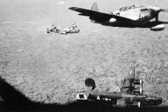 A pilot of the 100th Fighter Squadron shows off for the camera, buzzing by a B-24 Liberator as they return from an escort mission. Although it is a myth that the Tuskegee Airmen never lost a single bomber they escorted, they nevertheless had a stellar record in defending their charges with losses well below the average for all P-51 escorts, and were quite popular with Fifteenth Air Force bomber crews. (Collection of Frank Ambrose)