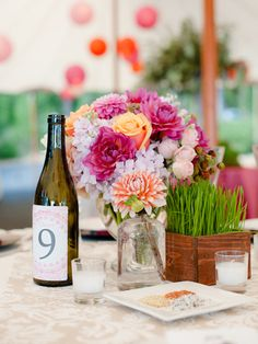 Wheatgrass planters nestled with low centerpieces and wine-bottle table numbers created a varied display. Low Centerpieces, Bottle Centerpieces, Rustic Wedding Centerpieces, Wedding Reception Decorations, Centerpiece Ideas, Centrepieces, Wedding Receptions, Summer Wedding, Our Wedding