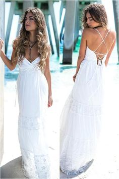 Tiered halter top maxi dress features embroidered lace flowers at the bust, knees, and hemline, an open back with criss-cross straps and a hidden zipper, an ope