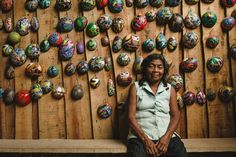 Indigenous woman in Costa Rica. Sitting in front of a wall of handcrafted boruca masks.