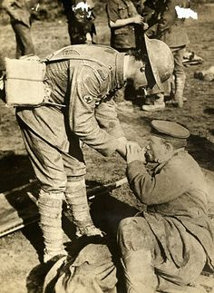 WWI British soldier is giving a wounded German a light, ca. 1918.